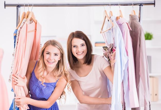 Mujeres jovenes hermosas que se colocan cerca del estante con las suspensiones.