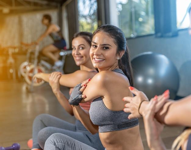 Mujeres jovenes hermosas que estiran en un gimnasio.