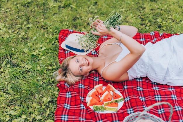 Mujeres jovenes hermosas que ponen en la tela escocesa cerca de la sandía, sosteniendo las flores. naturaleza, picnic.