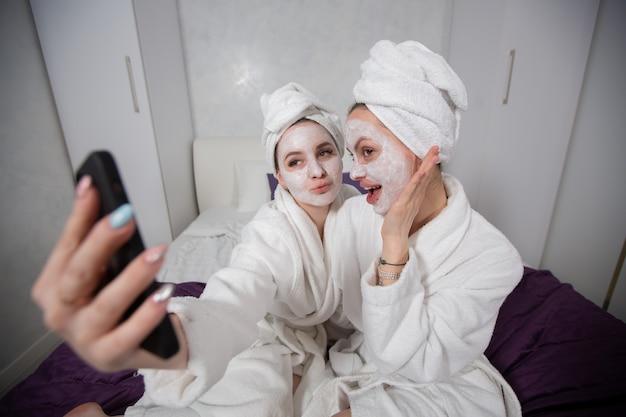 Las mujeres jóvenes homosexuales se toman selfies con máscaras faciales y batas blancas se divierten en casa concepto de belleza y cuidado personal de alta calidad