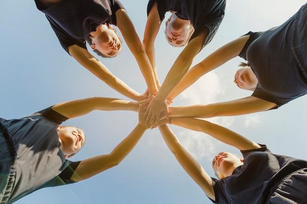 Mujeres jóvenes juntando las manos