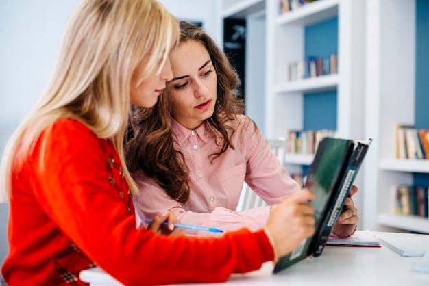 Mujeres jóvenes leyendo libros de texto juntos