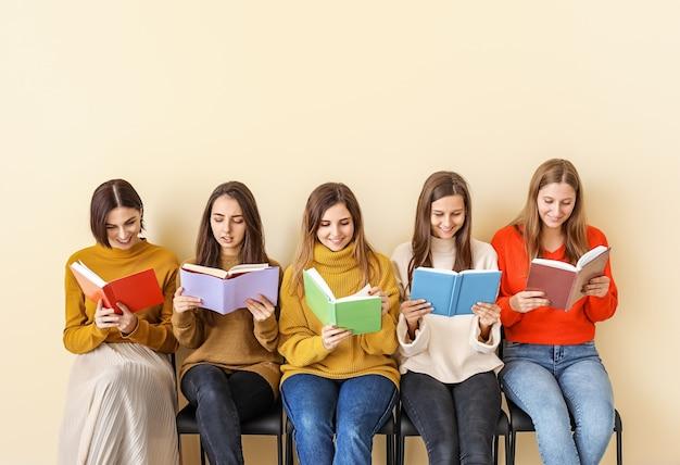 Mujeres jóvenes con libros sentados cerca de la pared de color