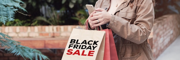 Mujeres jóvenes llevando bolsas de compras y comprando en línea