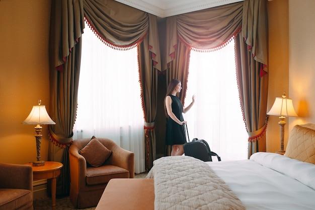 Mujeres jóvenes con maleta se alojan en una habitación de hotel
