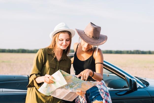 Mujeres jóvenes con mapa cerca de cabriolet