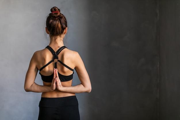 Las mujeres jóvenes meditando con namaste mudra firman en clase de yoga.