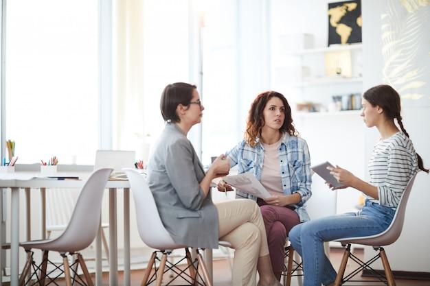 Mujeres jóvenes modernas discutiendo negocios