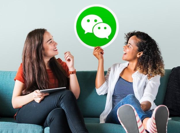 Mujeres jóvenes mostrando un ícono de wechat