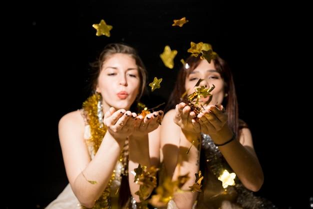 Mujeres jóvenes con oropel que sopla sobre adornos de papel estrellas