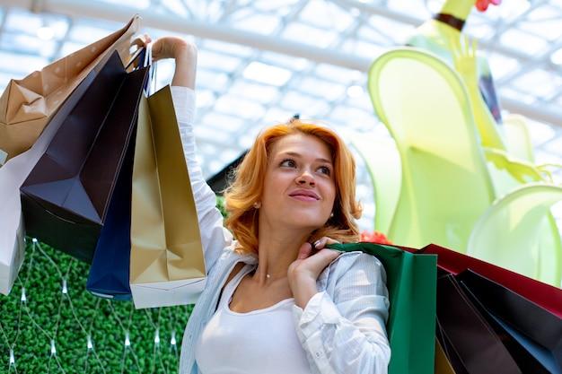 Mujeres jóvenes con paquetes de compras en el moderno centro comercial. concepto de compras concepto de viernes negro. mujer feliz celebración de paquetes. paquete del centro comercial en manos.