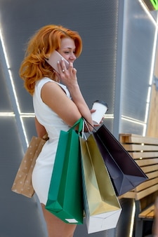 Mujeres jóvenes con paquetes de compras en el moderno centro comercial