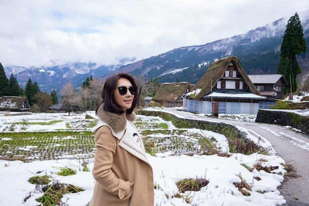 Mujeres jóvenes con patrimonio aldea de granja de madera rodeada de japón