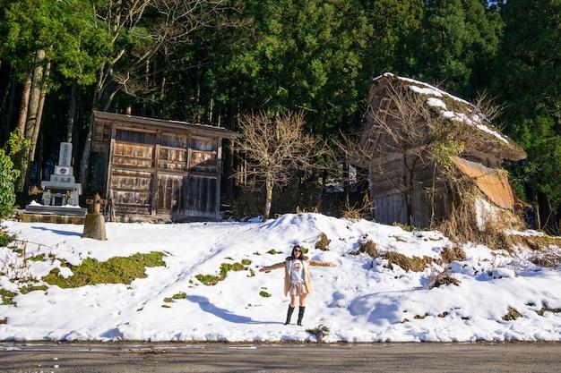 Mujeres jóvenes con patrimonio fondo de granja de madera en el famoso pueblo de japón.