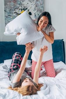 Mujeres jóvenes peleando por almohadas.