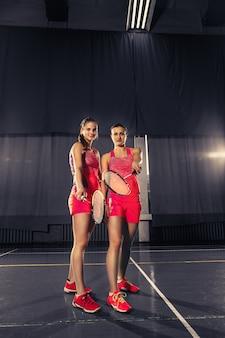 Mujeres jóvenes posando después de jugar bádminton en el gimnasio