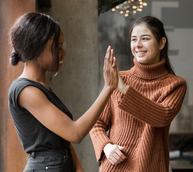 Mujeres jovenes positivas que tocan las manos