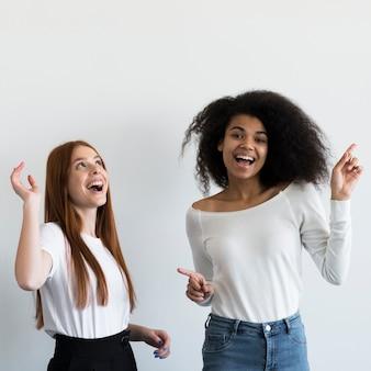 Mujeres jóvenes positivas riendo juntas