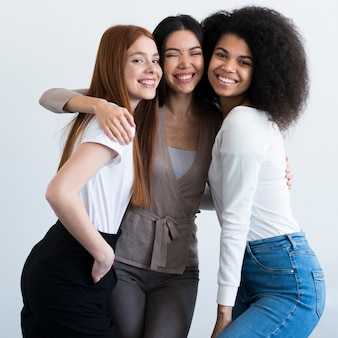 Mujeres jóvenes positivas sonriendo juntos