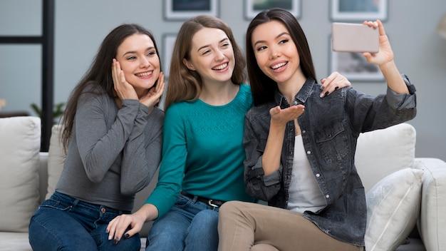 Mujeres jóvenes positivas tomando una selfie juntos