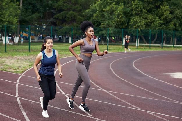 Las mujeres jóvenes practican deportes en el estadio.
