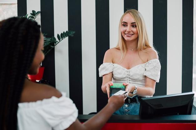 Mujeres jóvenes que pagan por compras