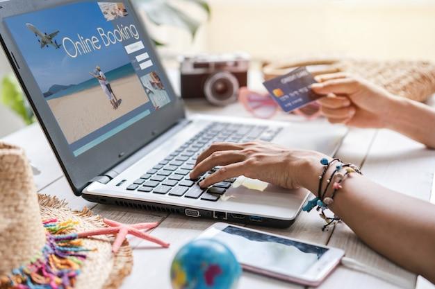 Mujeres jóvenes que planean un viaje de vacaciones de verano y buscan información o reservan hotel y usan tarjeta de crédito