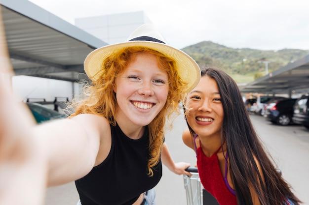 Mujeres jovenes que toman el selfie con la carretilla de las compras en estacionamiento