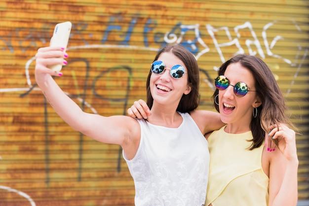 Mujeres jovenes que toman el selfie mientras que se coloca en la calle urbana
