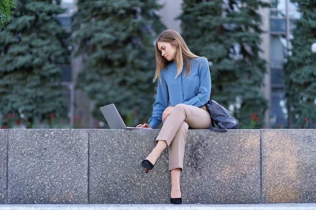 Mujeres jóvenes que trabajan en la computadora portátil en la plaza de la ciudad