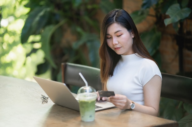 Mujeres jóvenes que usan computadora portátil y compras en línea con tarjeta de crédito, concepto de comercio electrónico