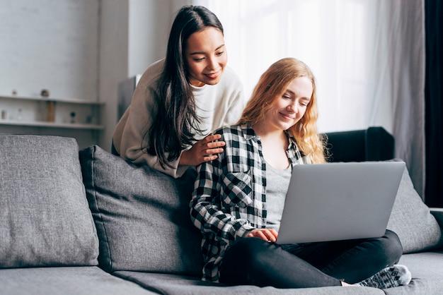 Mujeres jovenes que usan el ordenador portátil en casa