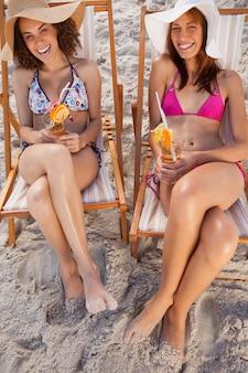 Mujeres jóvenes riendo en tumbonas mientras sostienen cócteles de frutas