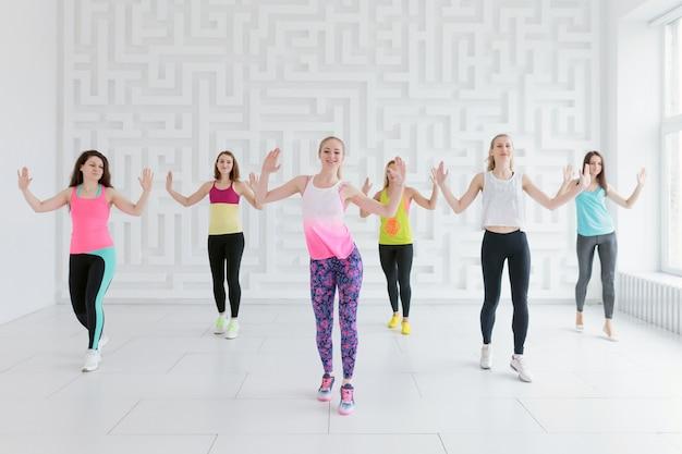 Mujeres jóvenes en ropa deportiva colorida en la clase de fitness de baile en el gimnasio blanco