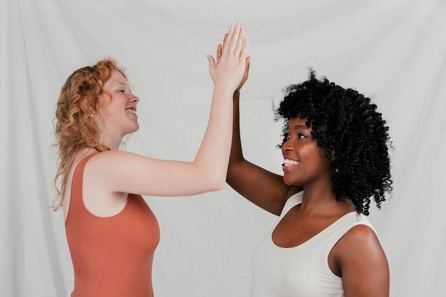 Mujeres jóvenes rubias y africanas que dan alta cinco contra el fondo gris
