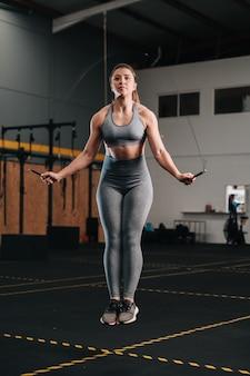 Las mujeres jóvenes saltando la cuerda mientras hacen ejercicio intenso