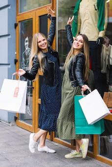 Mujeres jovenes satisfechas que sostienen los panieres que presentan delante de tienda de la ropa