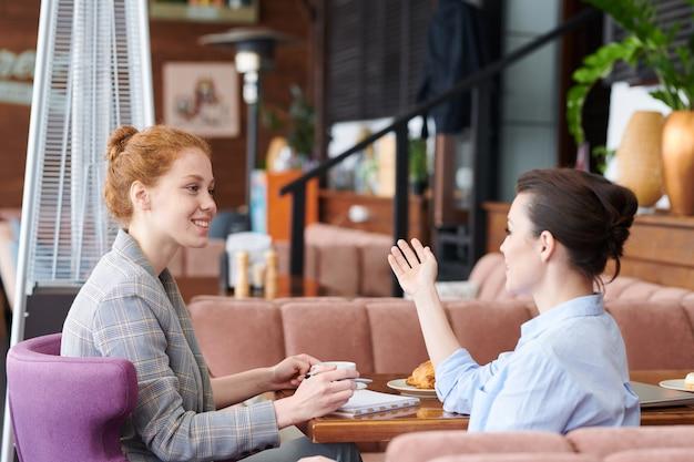 Mujeres jóvenes seguras de contenido sentadas a la mesa en un restaurante acogedor y compartiendo ideas durante el almuerzo