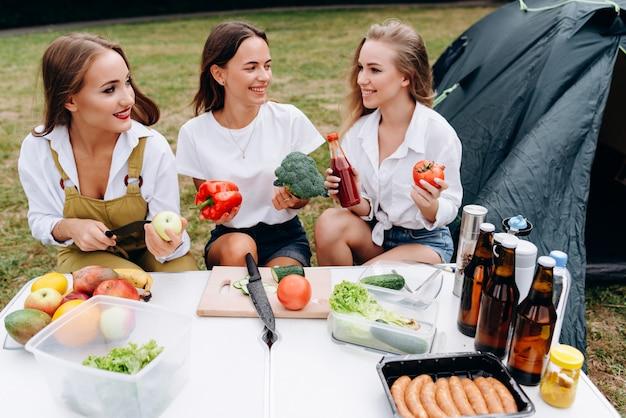 Las mujeres jóvenes sentados a la mesa y cocinar sonriendo y mirándose