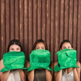 Mujeres jóvenes con sombreros de san patricio cerca de la cara