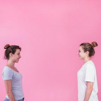 Mujeres jóvenes sonrientes de pie cara a cara mirando el uno al otro sobre fondo rosa