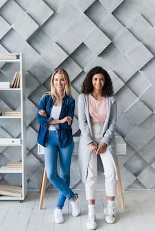 Mujeres jovenes sonrientes que se colocan en oficina