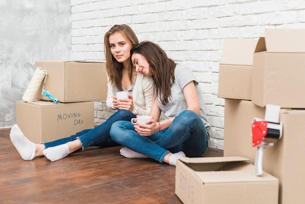 Mujeres jovenes sonrientes que se sientan en el piso que sostiene las tazas de café en la mano que se sienta entre el apilado de cajas de cartón