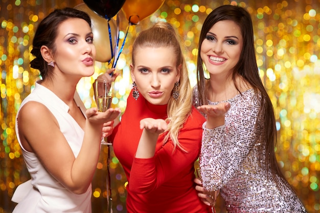 Mujeres jóvenes soplando besos, celebrando el año nuevo