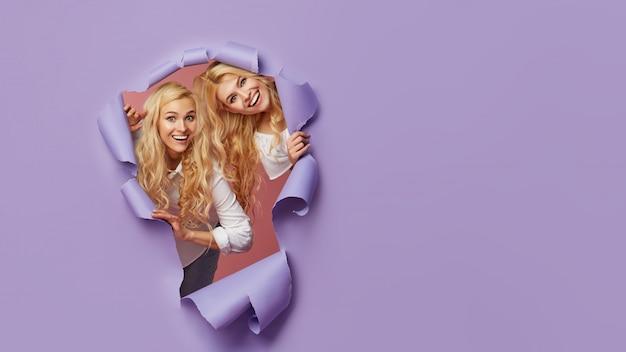 Las mujeres jóvenes sorprendidas se paran en un agujero de papel rasgado, tienen una expresión alegre y excitada, miran a través del avance de la pared púrpura.
