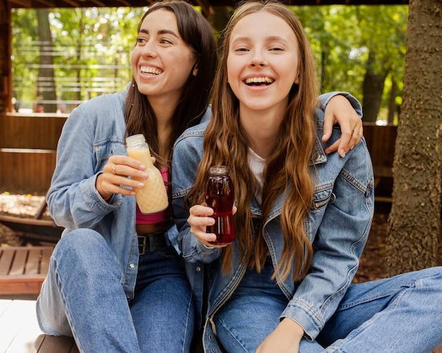 Mujeres jóvenes sosteniendo botellas de jugo fresco y riendo