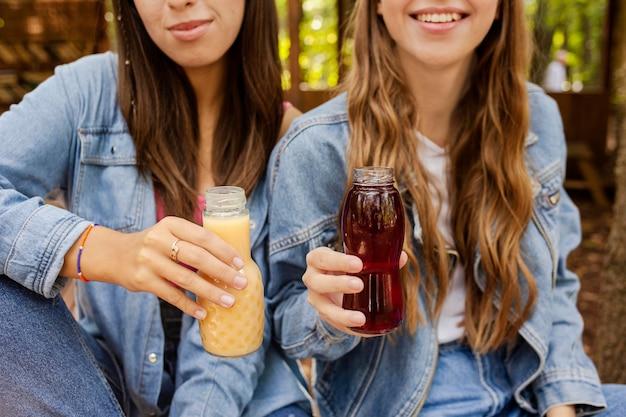 Mujeres jóvenes sosteniendo botellas de jugo fresco