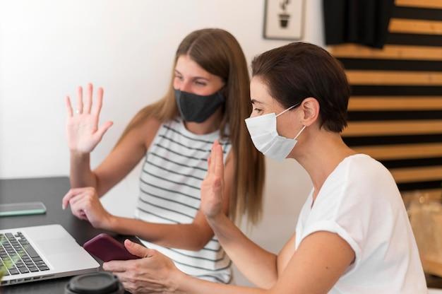 Mujeres jóvenes en la terraza con máscara