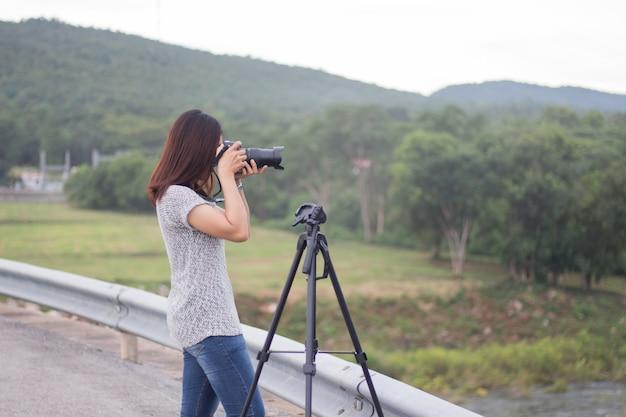 Las mujeres jóvenes toman fotos del paisaje.