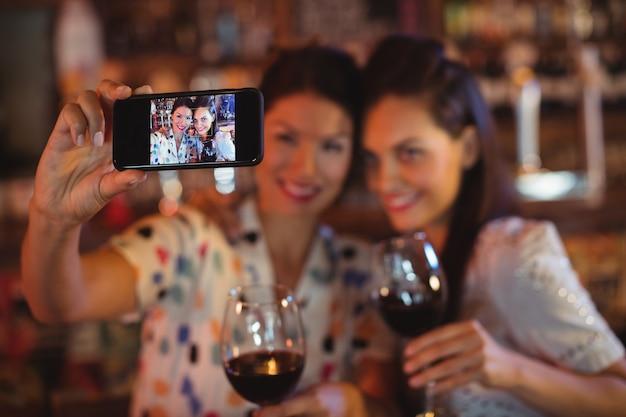 Mujeres jóvenes tomando un selfie desde teléfono móvil mientras toma un vino tinto